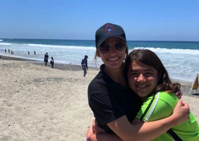 Program director hugging a student on the beach